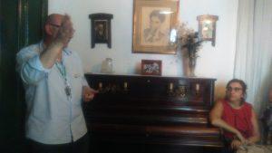 Teresa Ramos apoyada en el piano, escuchando muy atentamente las explicaciones del guía de la casa museo.